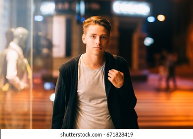 Attractive man walks through streets at night. Young guy going home in big city through showcase with dummy