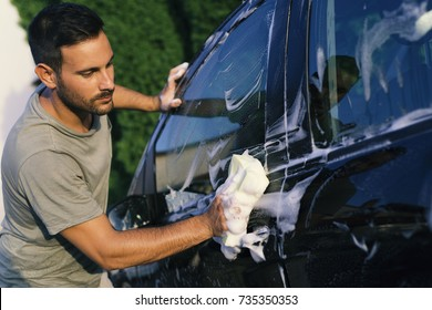 Attractive man washing car with sponge, soap and water