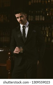 Attractive man wearing black tuxedo in whiskey bar.