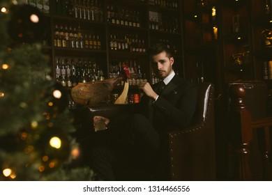 Attractive man wearing black tuxedo in whiskey bar, sitting beside Christmas tree.
