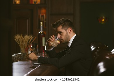 Attractive man wearing black tuxedo in whiskey bar.