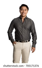Attractive man wearing a gray shirt and beige pants with a belt, standing against a white background with a smile on his face.