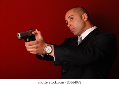 Attractive man wearing a suit aiming a gun. Red background.