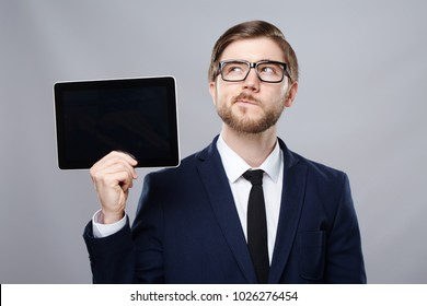 Attractive man wearing suit and glasses at studio background holding a tablet and thinking, business concept, copy space, portrait, mock up.