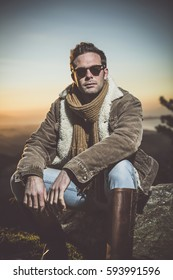 Attractive man wearing sunglasses, scarf and a brown sweater. Male model posing  in mountain.