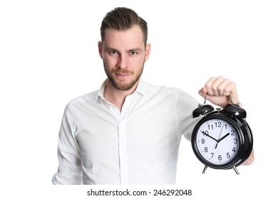 An attractive man wearing a white shirt holding a big clock, standing against a white background.