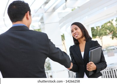 Attractive man and woman business team shaking hands at office building