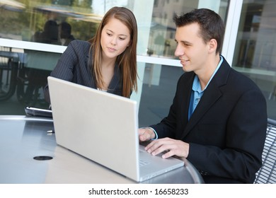 Attractive man and woman business team on laptop computer