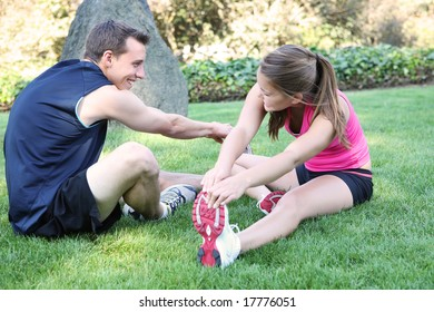 An attractive man and woman couple stretching in the park