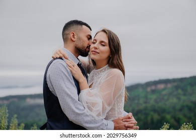 attractive man and woman cuddling tenderly in nature. romance in the relationship of a married couple. - Shutterstock ID 2029756349