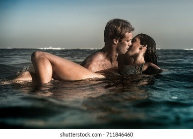 An attractive man and woman embrace and kiss in the seaside ocean in a romantic beach paradise.