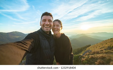 The attractive man and a woman taking a selfie on the mountain background