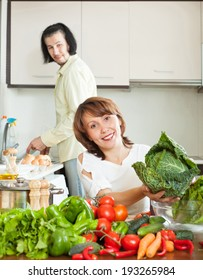 An attractive man and woman with vegetables in the kitchen of his home
