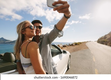 Attractive man and woman wearing sunglasses taking selfie photo together while standing by car on highway.