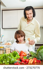 Attractive man and a young woman with vegetables in the kitchen of his home