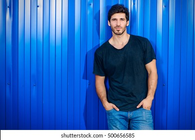 Attractive masculine man standing on a city street by a blue metal fence.  Male beauty 4950192d222a