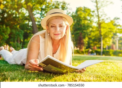 Attractive mature blonde haired woman lying on the grass at the park smiling reading a magazine relaxing outdoors copyspace information lifestyle stylish fashion maturity sensuality seasonal weekend