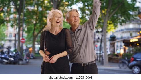 Attractive mature couple hailing a cab in Paris
