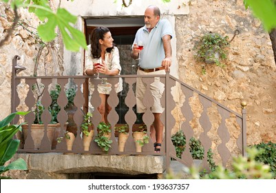 Attractive mature couple on a wooden staircase in a luxury hotel holiday villa green garden on vacation, drinking a glass of wine together and smiling having a conversation. Outdoors senior lifestyle.