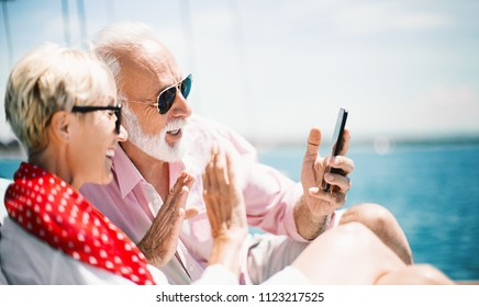 Attractive mature couple on a yacht video calling to their grandchildren. Side view. Horizontal.