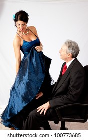 Attractive, mature couple in romantic mood, she is holding her long dress up so he can get a peek underneath.