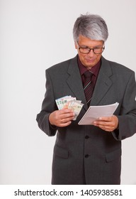 attractive mature European (Caucasian) slim businessman with short grey hair, grey suit, glasses, tie and purple shirt with money in his hand looks at a paper notebook in front of white background