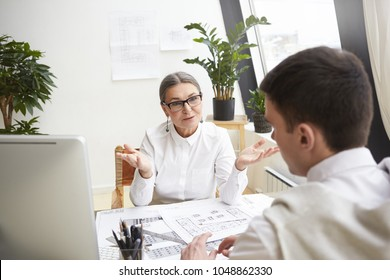 Attractive mature female CEO in glasses and white shirt sitting at her workplace and interviewing young talented male applicant for chief atchitect position, asking him about job experince and skills