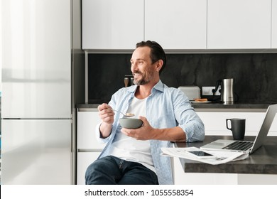 Attractive mature man having healthy breakfast while sitting at the kitchen table with laptop computer at home