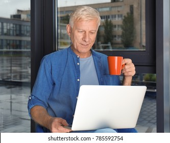 Attractive mature man with laptop computer indoors