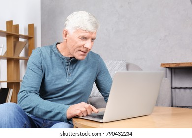 Attractive mature man with laptop indoors