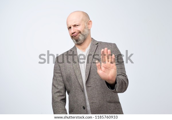 Attractive mature man showing refusal gesture. It is not for me, leave me in piece, has angry expression, poses against white concrete studio background