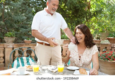 Attractive mature tourists couple having a luxurious continental breakfast in a hotel garden on a sunny day on holiday. Senior people eating healthy food and enjoying life, laughing. Lifestyle.