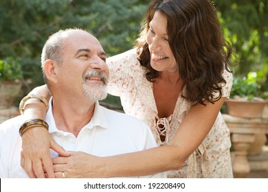 Attractive mature tourists couple sitting in a green garden during a sunny day on a summer holiday enjoying each others company, hugging and loving outdoors. Joyful senior people travel and lifestyle.