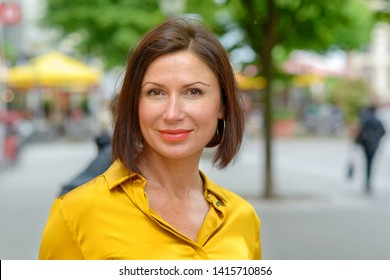 Attractive mature woman in colorful yellow shirt enjoying a day in town standing in a quiet urban square smiling at the camera