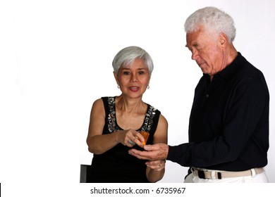 Attractive mature woman giving pills from a prescription container to her husband