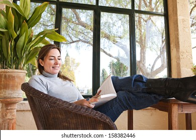Attractive mature woman with her feet up on a table, sitting in a home conservatory with large glass windows and a green garden, reading a book and relaxing indoors, smiling.