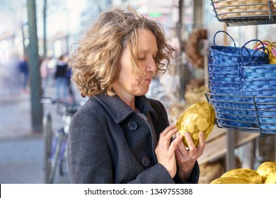Attractive mature woman looking at a golden painted hand crafted Easter egg at a market stall in a city street with a smile of nostalgia