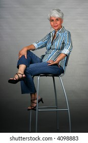 Attractive mature woman posing on a stool