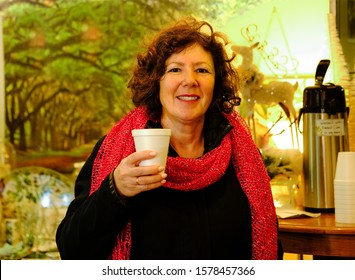 Attractive mature woman in red scarf drinking hot beverage and smiling into camera; carafe in background
