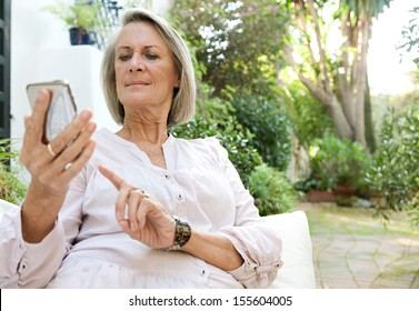 Attractive mature woman relaxing on a green garden and sitting on a white sofa holding and using a smartphone mobile device with touch screen, outdoors.
