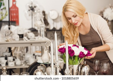Attractive mature woman shopping for flowers at the home decor boutique copyspace coziness comfort living lifestyle elegance apartment modern decorative design indoors customer shopper buying.