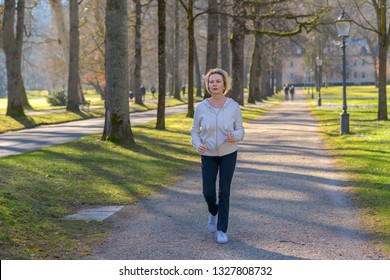 Attractive mature woman taking her daily jog through a wooded park approaching the camera along a tree lined avenue in a health and fitness concept