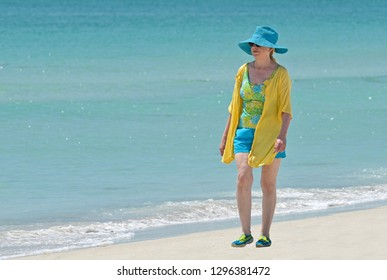 Attractive Mature Woman Walking on The Beach in Very Fashionable Attire