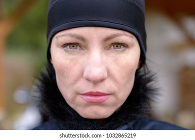 Attractive mature woman wearing a black winter hat staring at the camera with a penetrating look and deadpan expression