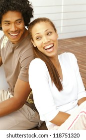 Attractive merry young ethnic couple having a good laugh while seated back to back on a brick patio