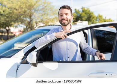 Attractive mid adult owner standing near the open door of modern car
