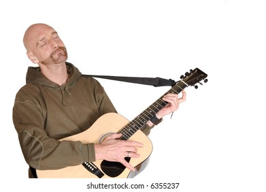 Attractive, mid fifties bearded middle aged man playing the guitar.  Casual dressed.