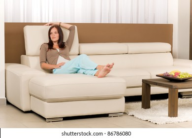 Attractive mid-aged woman relax modern living room on leather sofa