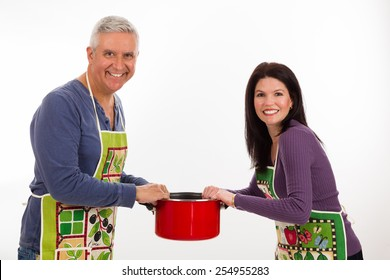 Attractive middle age couple wearing aprons and holding a pot on a white background.