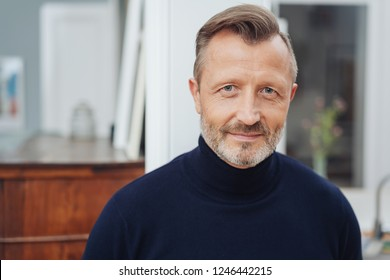 Attractive middle age man with stubble beard and stylish haircut, wearing black turtleneck and looking at camera with friendly smile. Closeup front bust portrait, with blurred room interior